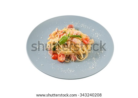 Pasta with bacon and tomato in grey ceramic dish isolated on white background with clipping path - stock photo
