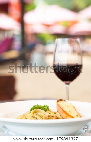 Pasta with basil sauce and garlic bread with wine