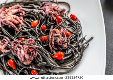 Pasta with black cuttlefish ink and small octopuses - stock photo