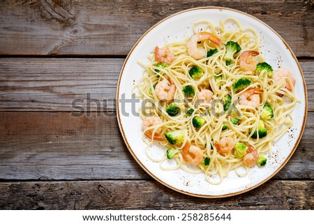 Pasta with broccoli and shrimp on a plate, top view - stock photo