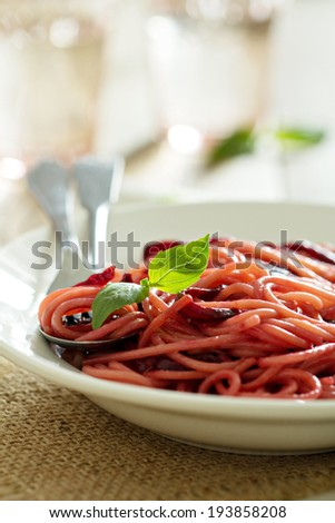 Pasta with caramelized beetroot served in a plate - selective focus - stock photo