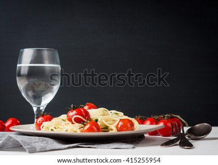 Pasta with cherry tomatoes on the wooden background