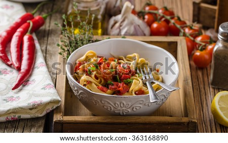 Pasta with cherry tomatoes pesto, chilli and herbs