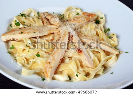 Pasta with chicken pieces in a white bowl - stock photo