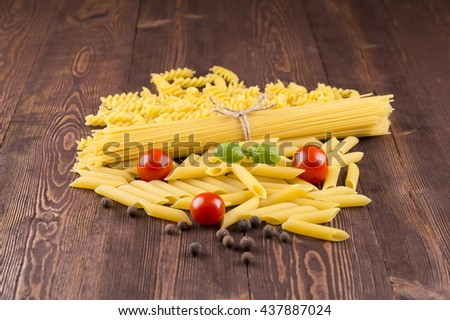 Pasta with different types of italian pasta. Uncooked pasta  on the table. mixed dried pasta selection and cherry tomatoes, basil, sweet peas - stock photo