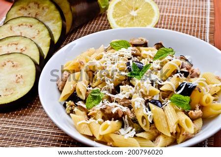 Pasta with eggplant, tuna, mint and ricotta salata. Recipe of Italian cuisine - stock photo