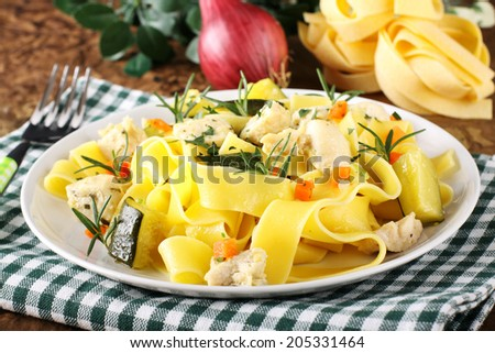 Pasta with fish, zucchini and carrots on complex background - stock photo