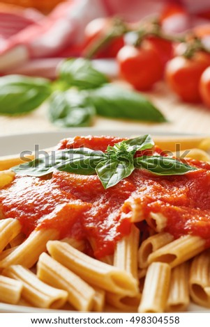 Pasta with fresh tomato sauce and basil in white dish close up - basil and tomato in background