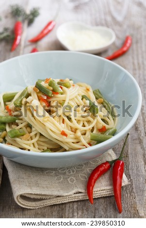 Pasta with green beans, nuts and chilli - stock photo