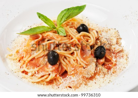 pasta with ham, mushrooms, olive, basil leaf and  parmesan, on white plate - stock photo