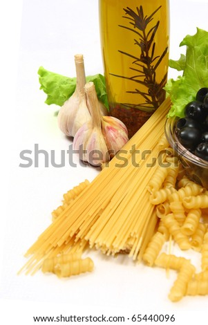 Pasta with herbs and black olives isolated on a white background.