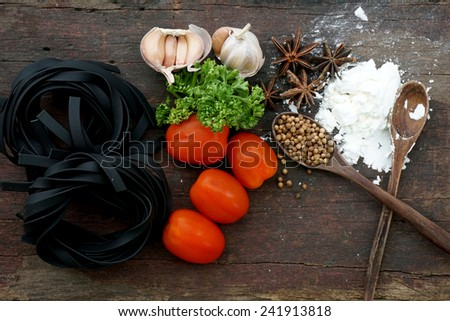 Pasta with ingredients like flour, tomato, garlic and pepper - stock photo
