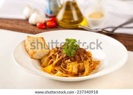 Pasta with meat sauce and garlic bread - stock photo