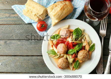 Pasta with meatballs on plate, glass of red wine on wooden  table background - stock photo