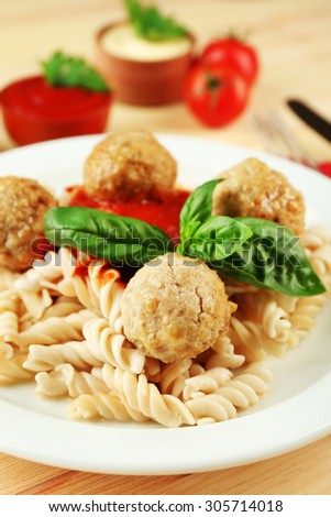 Pasta with meatballs on plate, on wooden  table background - stock photo
