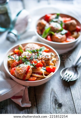 Pasta with meatballs on rustic background - stock photo