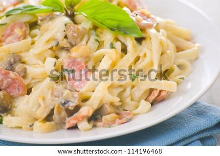 Pasta with mushrooms, smoked sausage and cream sauce with basil - stock photo