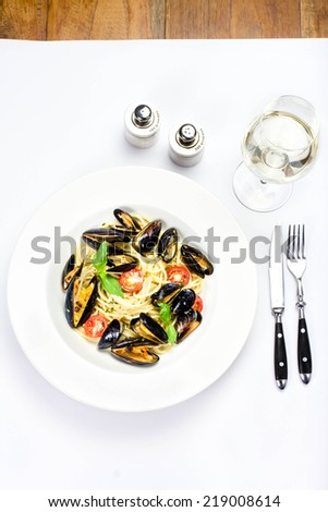 Pasta with mussels, cherry tomatoes  and herbs for a tasty sea food meal macro. Restaurant Studio Image. - stock photo