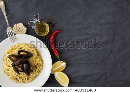 Pasta with mussels, lemons, chili pepper and spices - stock photo