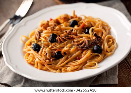 Pasta with octopus and olives - stock photo