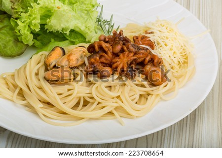 Pasta with octopus, mussels and fresh herbs - stock photo