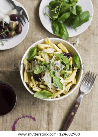 Pasta with Olives, Herbs and Parmesan. Rustic setting. - stock photo