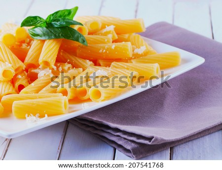 Pasta with parmesan and basil, over white plate