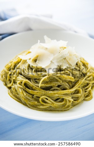 Pasta with pesto and parmesan on blue wooden background close up. Italian cuisine. - stock photo