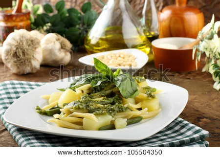 Pasta with pesto, green beans and potatoes on complex background - stock photo