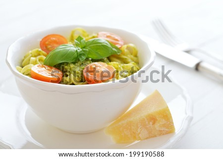 Pasta with pesto sauce and basil on white plate