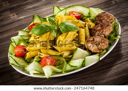 Pasta with pesto sauce, meatballs, parmesan and vegetables - stock photo