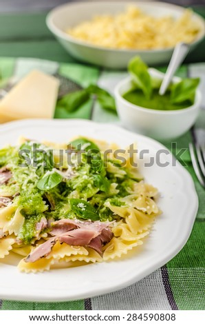 Pasta with pesto, smoked bacon and basil. Domestic pesto with oil, basil, nuts, garlic and parmesan cheese.