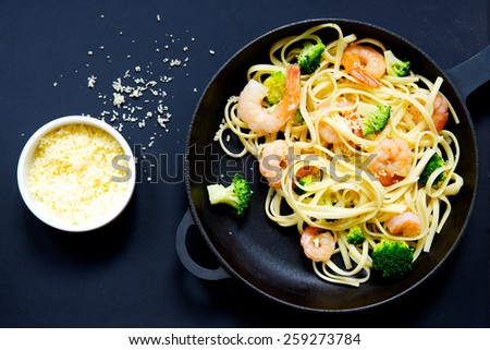 Pasta with prawns and broccoli in a frying pan on a black background - stock photo