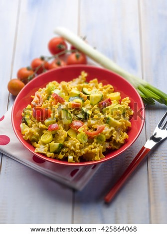 pasta with saffron cream sauce and sliced vegetables, selective focus - stock photo