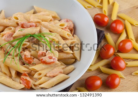 Pasta with salmon and cherry tomatoes, garnished with fresh bunch of chives and surrounded by raw ingredients - stock photo
