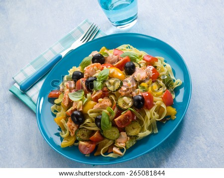 pasta with salmon zucchinis capsicum olives and tomatoes - stock photo