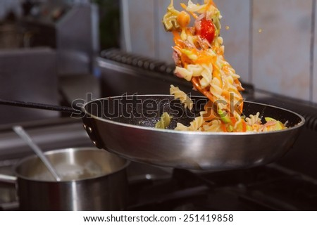 Pasta with sauce frying on pan