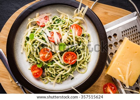Pasta with spinach, tomatoes and cheese on plate, studio shot - stock photo