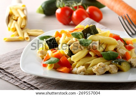 Pasta with swordfish, zucchini and cherry tomatoes on complex background - stock photo