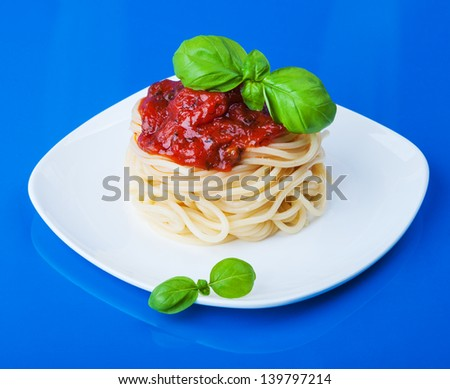 Pasta with tomato sauce and basil on table - stock photo