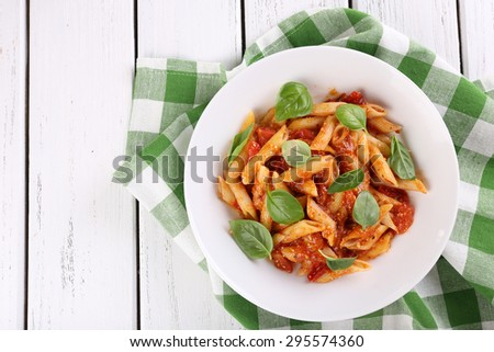 Pasta with tomato sauce and basil on table close up - stock photo