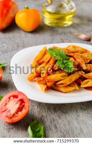 pasta with tomato sauce and basil on wooden background