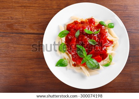 Pasta with tomato sauce and basil on wooden table close up - stock photo