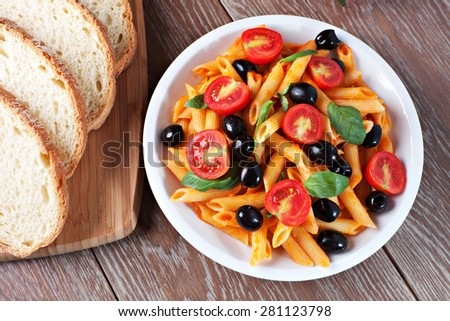 Pasta with tomato sauce and olives - stock photo