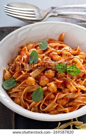 Pasta with tomato sauce, chickpeas and cardamom - stock photo