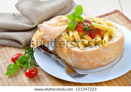 Pasta with tomato sauce filled in an Italian ciabatta loaf