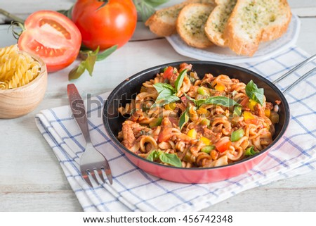 Pasta with tomato sauce in pan.