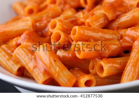 Pasta with tomato sauce on whit plate, close up - stock photo