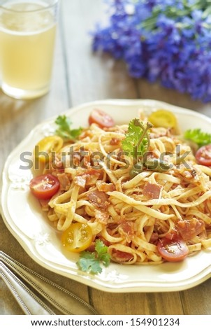 Pasta with tomatoes, ham, capers and cheese - stock photo