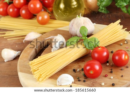 Pasta with tomatoes, olive oil and basil on wooden background
